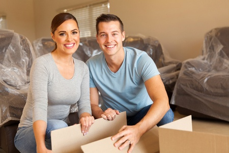 45857863 - happy young couple unpacking boxes and moving into a new home